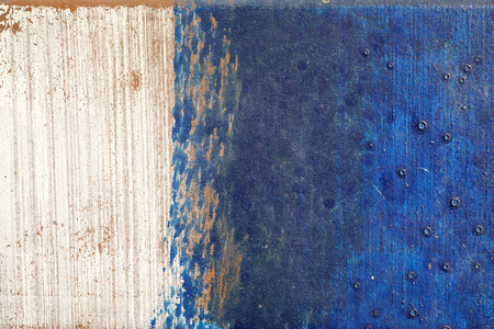 gravelly: Small part of plastered hoarse,scratched and peeled surface area with blue,yellowish-brown and white paint -Abstract background-Close up