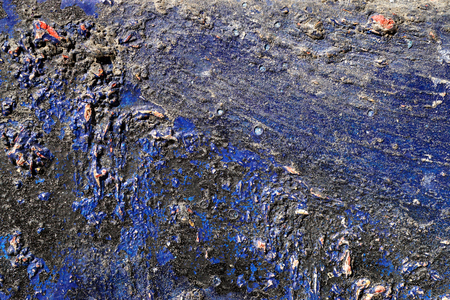 gravelly: Small part of plastered hoarse,scratched and peeled surface area with blue and black paint -Abstract background-Close up