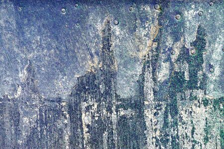gravelly: Small part of plastered hoarse,scratched and peeled surface area with blue and green paint -Abstract background-Close up