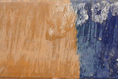gravelly: Small part of plastered hoarse,scratched and peeled surface area with blue and yellowish-brown paint -Abstract background-Close up