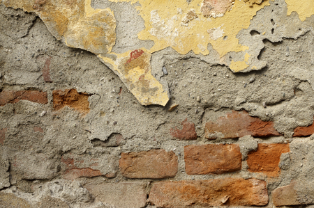 Close up of old, crumbling,cracked, grunge red-brick wall with mortar cement.  Several different layers of peeled  orange, beige, brown,grey,yellowish-brown and ocher facade  paint.  Detail abstract texture background with space for  text, copy, your word Stock Photo