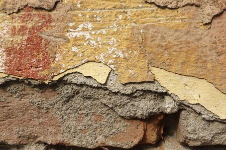 redbrick: Close up of old, crumbling,cracked, grunge red-brick wall with mortar cement.  Several different layers of peeled  orange, beige, brown,grey,yellowish-brown and ocher facade  paint.  Detail abstract texture background with space for  text, copy, your word Stock Photo