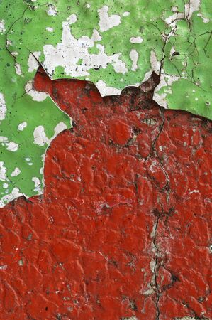 Close up of dirty,crumbling,red concrete wall   Old,grungy,rough surface with gravel structure  and layer of cracked and peeled white and green paint Abstract texture background space for copy or text Stock Photo