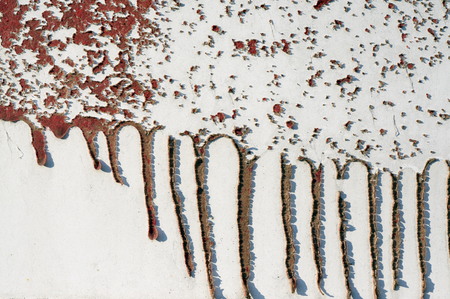 runny: Close up,macro photography of dripping, runny red color on rough,grungy, dirty metal fence with interesting, intensive shadows from the cracked paint  Abstract textured background with space for copy or text