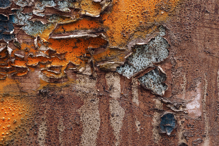 urban decay: Colorful tornripped old posters on grunge old metal surface  Creative abstract textured background -street wall art with orange,blue,black and brown paint.Close up, macro photo Stock Photo