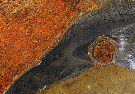 Close up of rusted, corroded and peeled old grunge rough  metal surface with rust stains - abstract textured brown, black and orange background