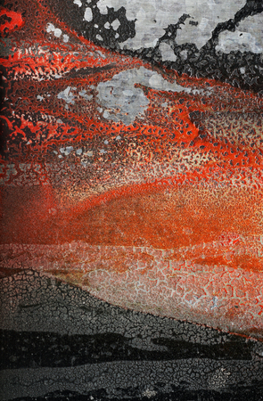 Relief forms on the wall formed by cracked, dried orange and black Vibrant paint. Abstract textured  grunge background-Close up. Rough,cracked surface with associative elements.  Association concept