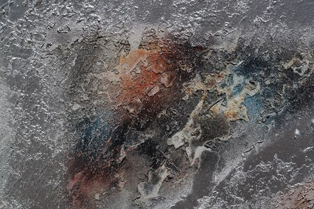 Abstract textured background. Grunge metal close up. Rusty, dirty old metal sprinkled with orange, blue, brown, grey and silver paint. Colorful, scratched, cracked and peeled layers. Macro.  Banco de Imagens