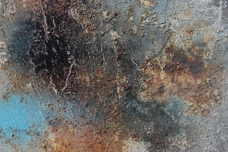 Abstract textured background. Grunge metal close up.Rusty, dirty old metal sprinkled with orange, blue, brown, grey and silver paint.Colorful, scratched, cracked and peeled layers. Macro.  스톡 콘텐츠