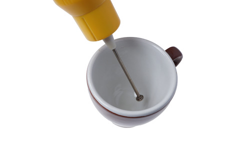 Electric beater and a cup isolated on white.  Handheld utensil, coffee frother and foam maker. Homemade instant coffee concept