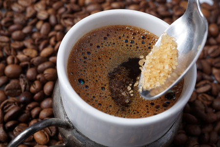 Close up of traditional homemade  Turkish coffee. Adding spoonful of granulated crystal brown sugar. Strong unfiltered coffee in white porcelain cup.  Coffee beans background. Tradition concept.  Stock Photo