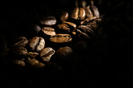 Coffee beans background.  Brown texture of roasted coffee seeds filling all frame.  Space for copy text. Selective spot light, back light, shallow depth of field, selective focus. Extreme close up.