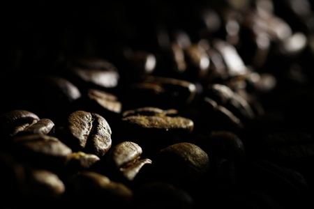 Coffee beans background. Brown texture of roasted coffee seeds filling all frame. Space for copy text.Selective spot light, back light, shallow depth of field, selective focus. Extreme close up. Stock fotó