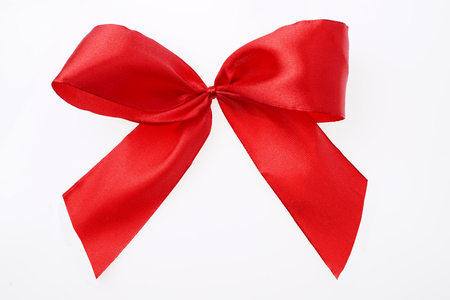 Textile ribbon tied in bow. Red satin. Isolated on white. Close up. Gift concept. Top view. Stock fotó