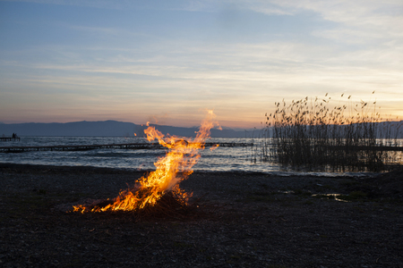 Sunset on a beach by the Lake Ohrid near Struga. Flame and smoke from burning of a cut reeds. Fire resembling a running man.  Reeds and wooden dock in the background. Stock fotó