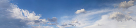 Blue sky with fluffy cumulus and stratus clouds panorama.  Cloudscape background.  Skyscape  background. Multiple photos digitally stitched.
