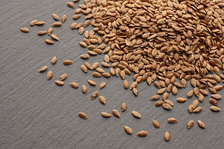 Raw organic flaxseeds. Close up of Linum usitatissimum seeds on dark stone background. Super seeds.  Healthy food concept.