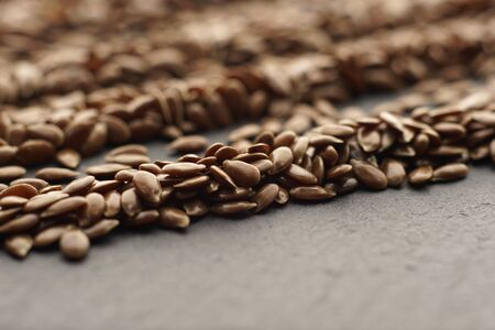 Raw organic flaxseeds. Close up of Linum usitatissimum seeds on dark stone background. Super seeds.  Selective focus. Healthy food concept. Stock fotó