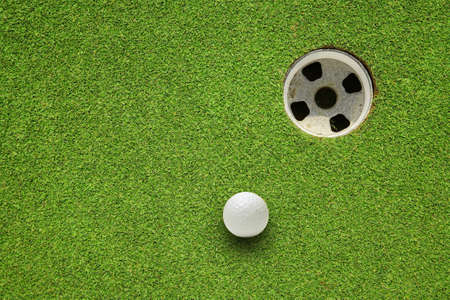 golf green: golf ball very close to the hole