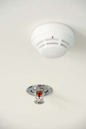 Sprinkler and smoke detector on the ceiling Stock Photo