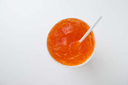 a straw: orange soda with drinking straw in disposable cup