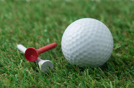 golf ball: golf ball with tee on grass Stock Photo