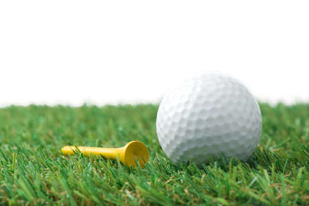 yellow ball: golf ball with tee on grass Stock Photo
