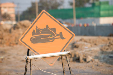 warning sign of construction vehicles on the road Stock Photo