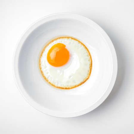 Huevo frito en un plato blanco aisladas sobre fondo blanco Foto de archivo - 62298235