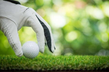 golf players hand placing ball on grass