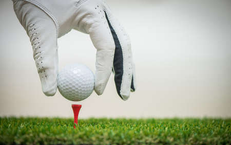 golf players hand placing ball on tee