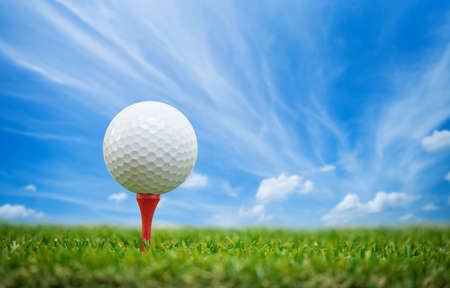 golf ball on tee with blue sky