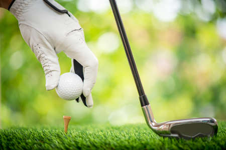 Golf players hand placing ball on tee Stock Photo