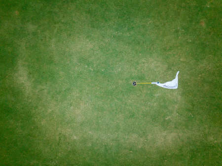aerial view of golf hole with flag in golf course. aerial view by flying drone
