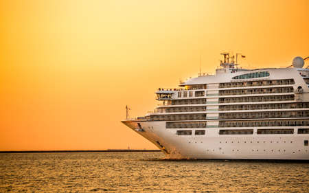 large cruise liner ship going from port with sunset background