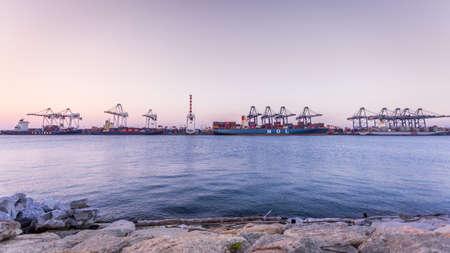Chonburi, Thailand - February 18, 2018 : Loading cargo container ship port at twilight in Sriracha industrial port, Chonburi, Thailand. Editöryel