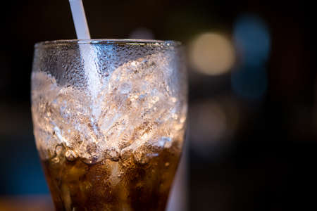 glass of half cola with ice and straw Stok Fotoğraf