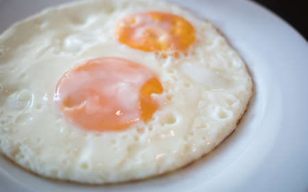 two fried egg on the white plate on breakfast table