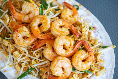 Fried noodle Thai style with prawns in a plate