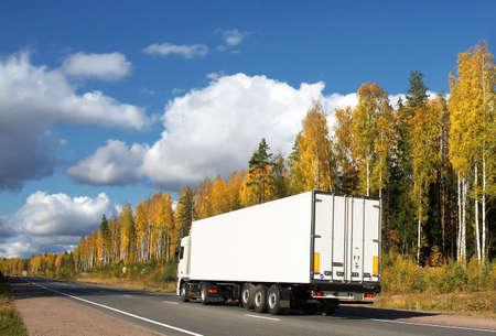 white truck on autumn highway Standard-Bild