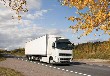 white truck on golden autumn highway, landscape photo