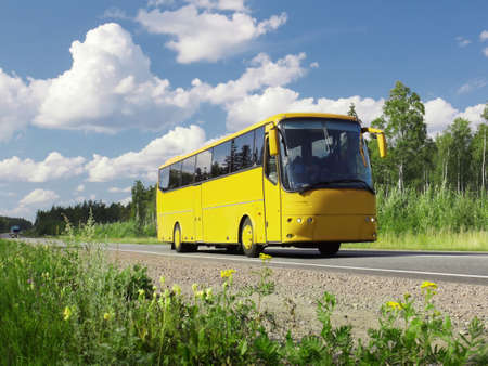 antrey: yellow tourist bus on  highway and summer country landscape Stock Photo