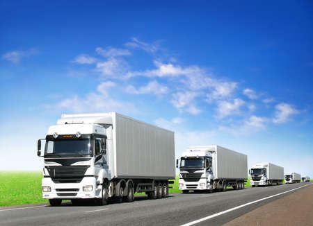 delivery truck: caravan of white trucks on country highway under blue sky Stock Photo