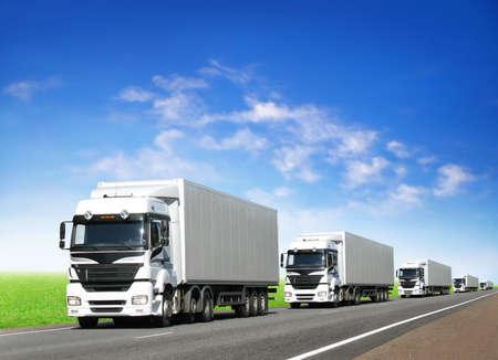 caravan of white trucks on country highway under blue sky Stock Photo