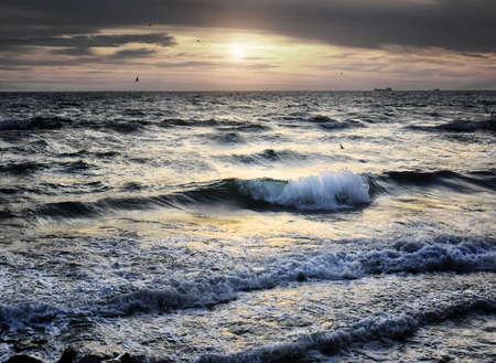 Meer-Welle und Sonnenuntergang mit Vögeln und Schiffe auf Hintergrund Lizenzfreie Bilder