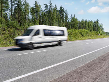 mini: white mini bus speeding on summer country highway, blured in motion Stock Photo