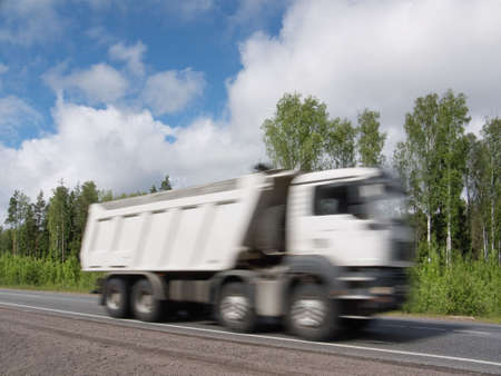 country highway: white dump truck speeding on country highway, blured in motion