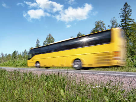 yellow tourist bus speeding on country highway, blured in motion, with reflecting sun Stock Photo