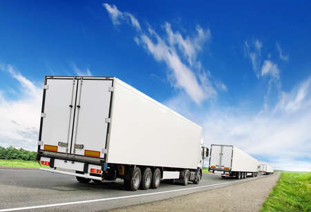truck on highway: caravan of white trucks on country highway under blue sky Stock Photo