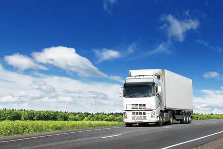 camion: blanco cami�n en la carretera de pa�s de verano bajo el cielo azul Foto de archivo